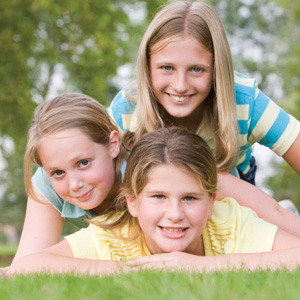 three-young-girl-friends-piled-on-each-other-outdoors-smiling-l