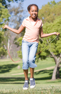 young-girl-using-skipping-rope-outdoors-smiling-m